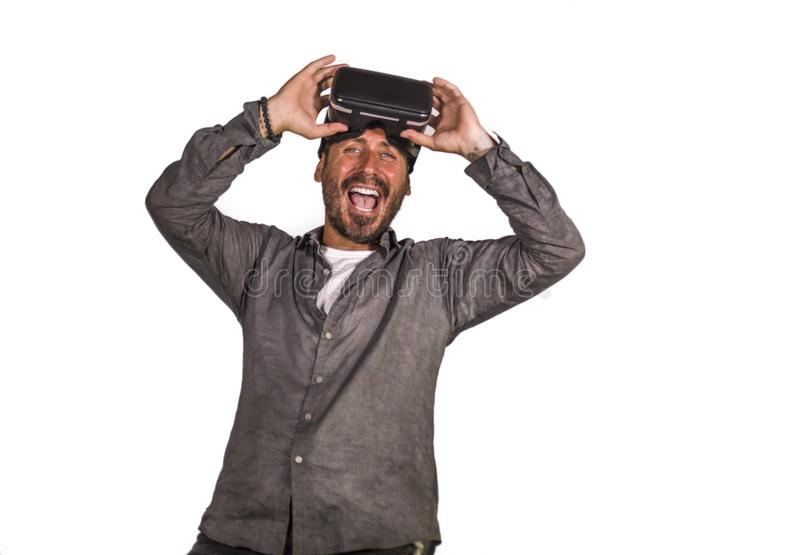 Young happy and excited man wearing virtual reality VR goggles headset experimenting 3d illusion playing video game enjoying the. Illusion environment surprised royalty free stock photos
