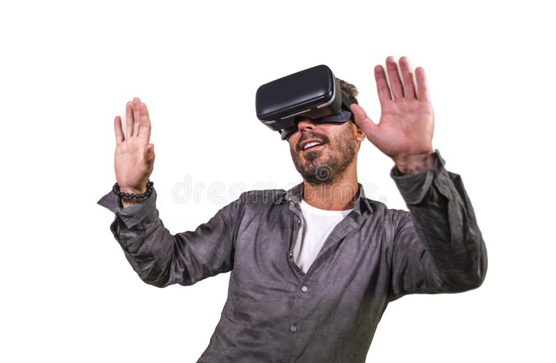 Young happy and excited man wearing virtual reality VR goggles headset experimenting 3d illusion playing video game touching. Illusion environment surprised stock photo