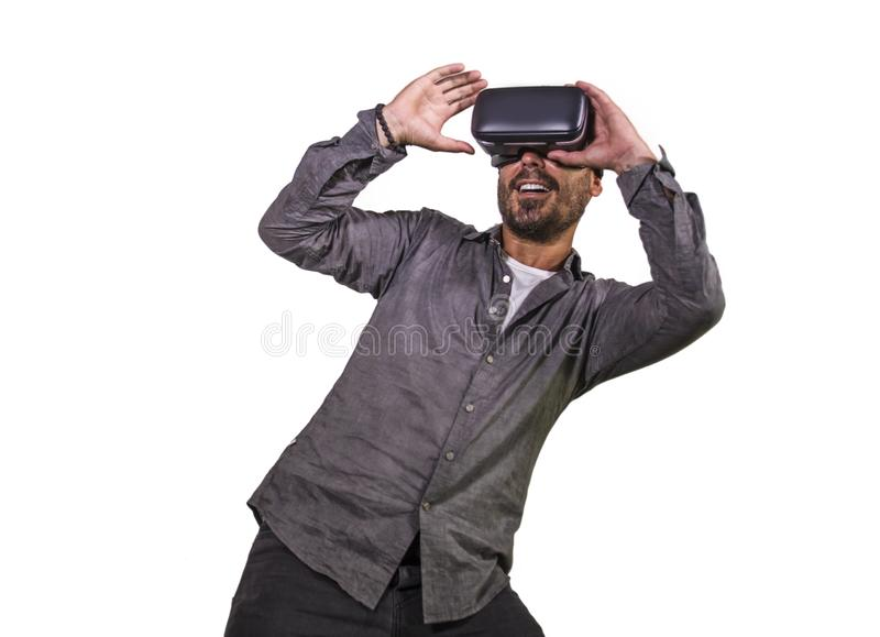 Young happy and excited man wearing virtual reality VR goggles headset experimenting 3d illusion playing video game touching. Illusion environment surprised stock image