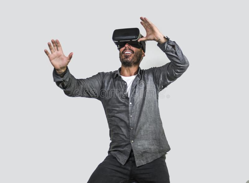 Young happy and excited man wearing virtual reality VR goggles headset experimenting 3d illusion playing video game touching. Illusion environment surprised royalty free stock image