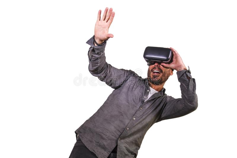 Young happy and excited man wearing virtual reality VR goggles headset experimenting 3d illusion playing video game touching. Illusion environment surprised royalty free stock photo