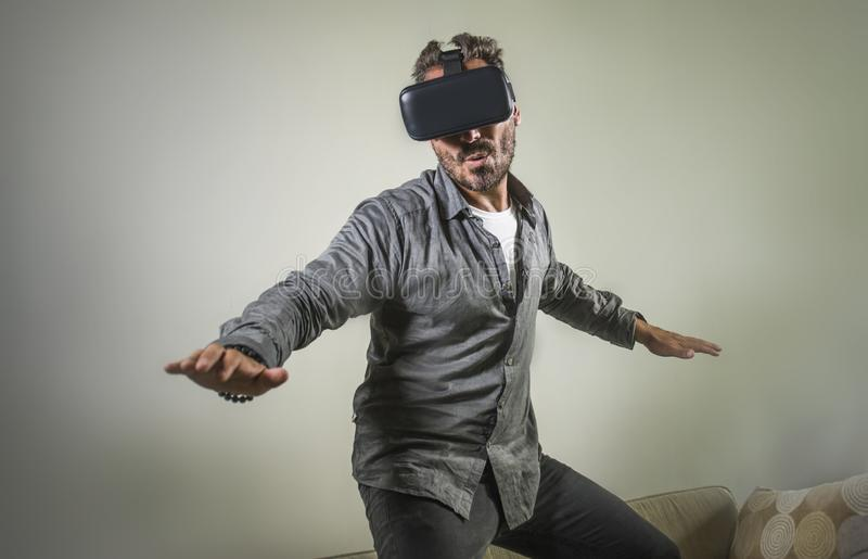 Young happy and excited man wearing virtual reality VR goggles headset experimenting 3d illusion playing video game touching. Illusion environment surprised at royalty free stock image