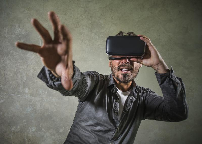 Young happy and excited man wearing virtual reality VR goggles headset experimenting 3d illusion playing video game touching. Illusion environment surprised  on royalty free stock photography