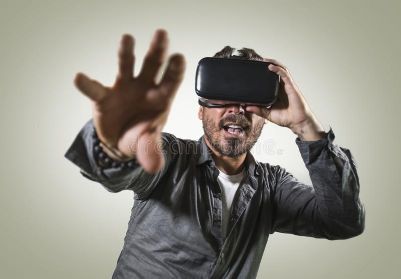 Young happy and excited man wearing virtual reality VR goggles headset experimenting 3d illusion playing video game touching. Illusion environment surprised  on stock photos