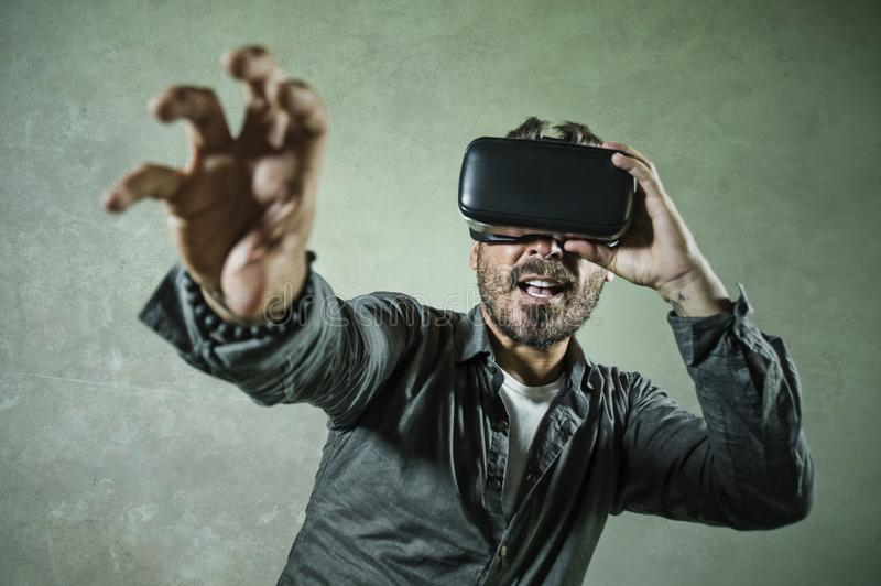 Young happy and excited man wearing virtual reality VR goggles headset experimenting 3d illusion playing video game touching. Illusion environment surprised royalty free stock photography