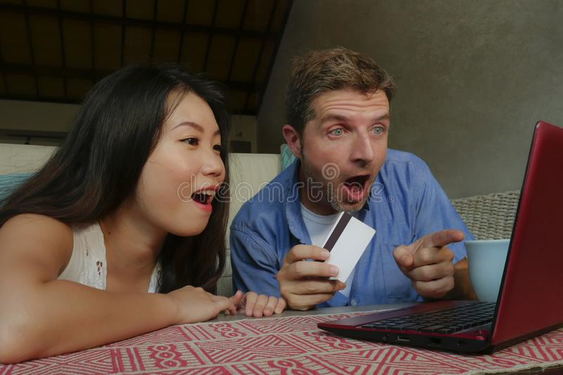 Young happy and excited mixed ethnicity couple with Asian Chinese woman and Caucasian man internet banking and online shopping wit royalty free stock image