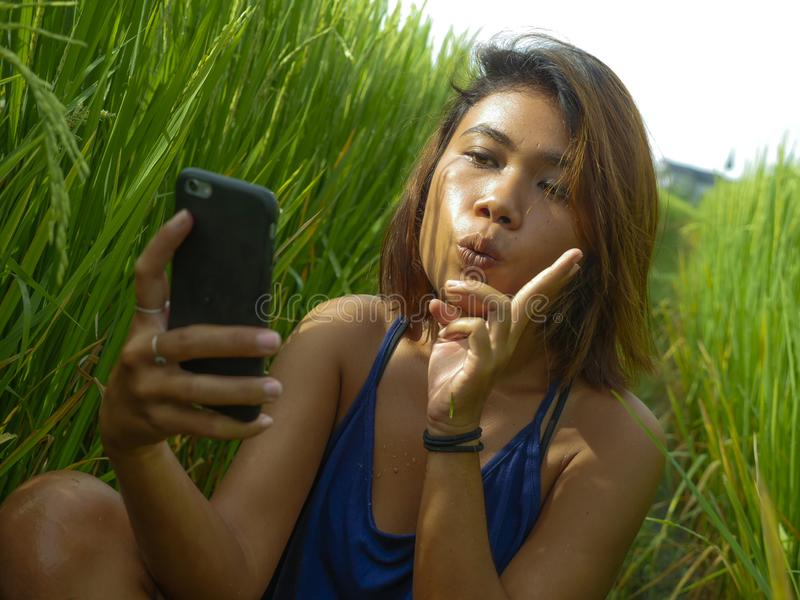 Young happy and exotic islander Asian girl from Indonesia taking selfie self portrait photo with mobile phone smiling cheerful and royalty free stock photography