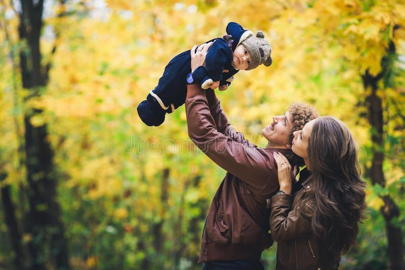 Young happy family in autumn in park. Father joyfully throws his son up. stock photo