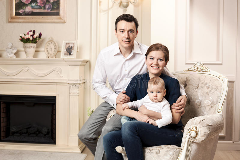 Young happy family with a baby indoors royalty free stock photography