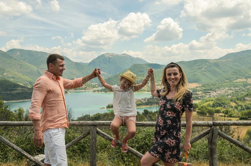 Young happy family on a background of a mountain lake Lago del Turano stock image