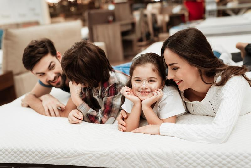 Young happy family checks on softness of orthopedic mattress, lying on bed in furniture store. Young couple with children buys mattress in store. Check royalty free stock image