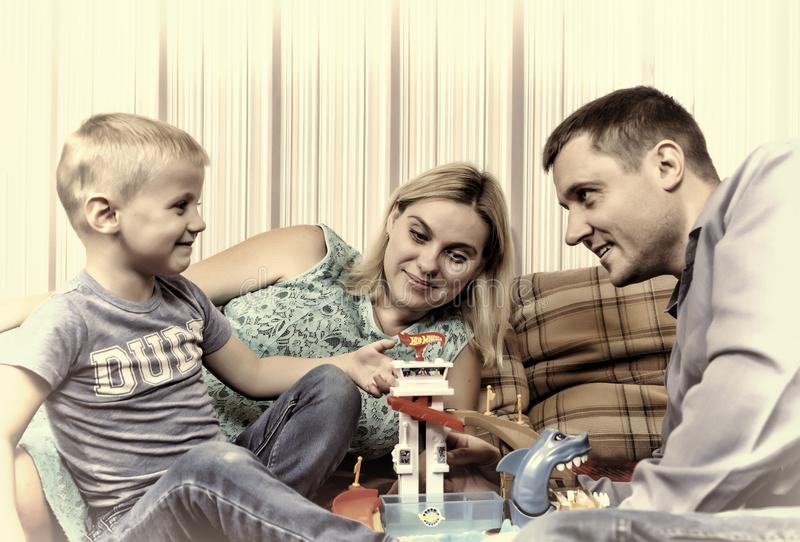 Young happy family with child is resting at home on the couch. stock photography