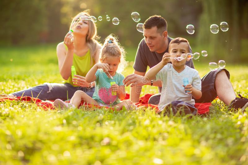 Happy family with children blow soap bubbles outdoor. Young happy family with children blow soap bubbles outdoor stock images