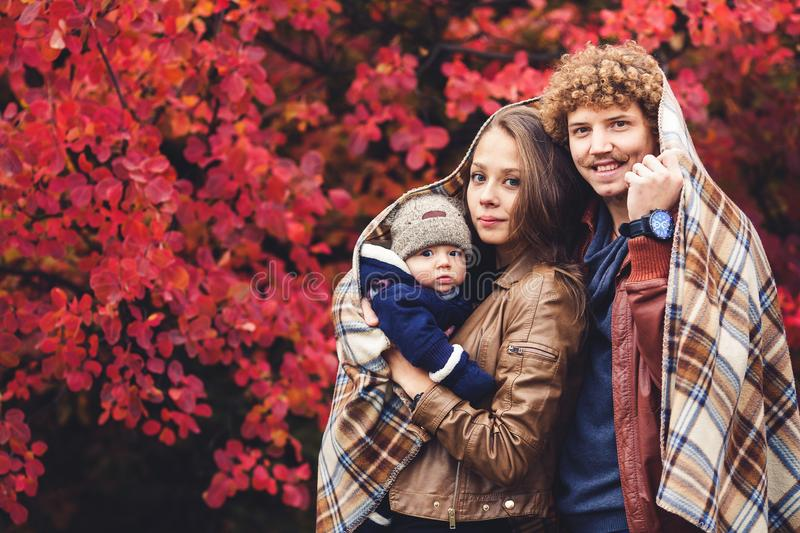 Young happy family, covered in blanket, stands near beautiful red autumn trees. Young happy family, covered in blanket, stands near beautiful red autumn trees royalty free stock photography