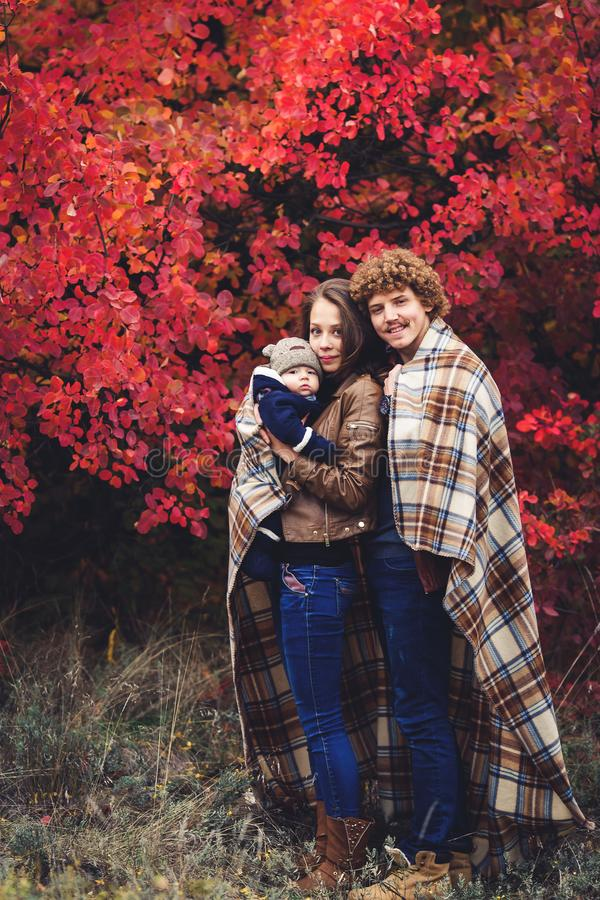 Young happy family, covered in blanket, stands near beautiful red autumn trees. Young happy family, covered in blanket, stands near beautiful red autumn trees stock photo