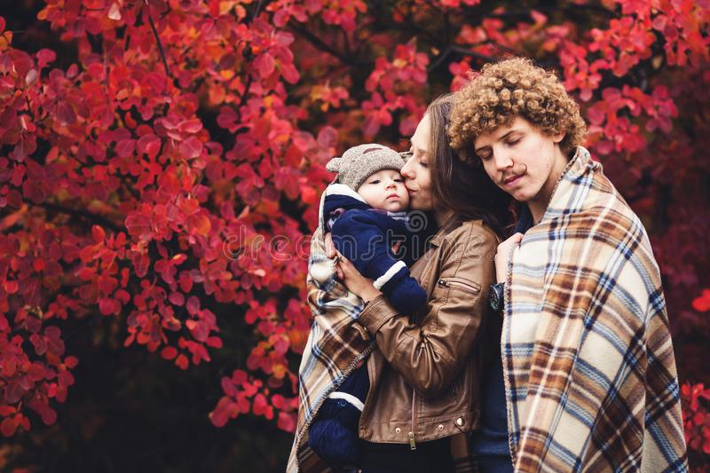 Young happy family, covered in blanket, stands near beautiful red autumn trees. Young happy family, covered in blanket, stands near beautiful red autumn trees royalty free stock images