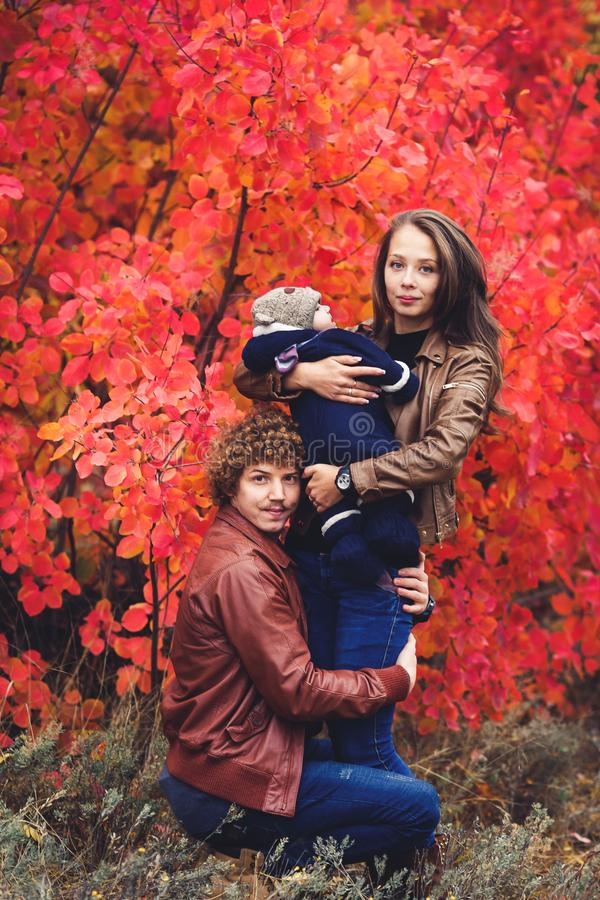 Young happy family, covered in blanket, stands near beautiful red autumn trees. Mom holds his son in his arms, and Dad hugs her legs royalty free stock image