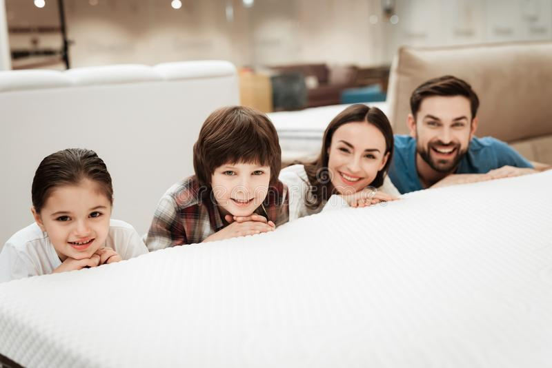 Young happy family hides behind bed in orthopedic mattress store. Testing softness of mattress. Choosing mattress in store stock photography