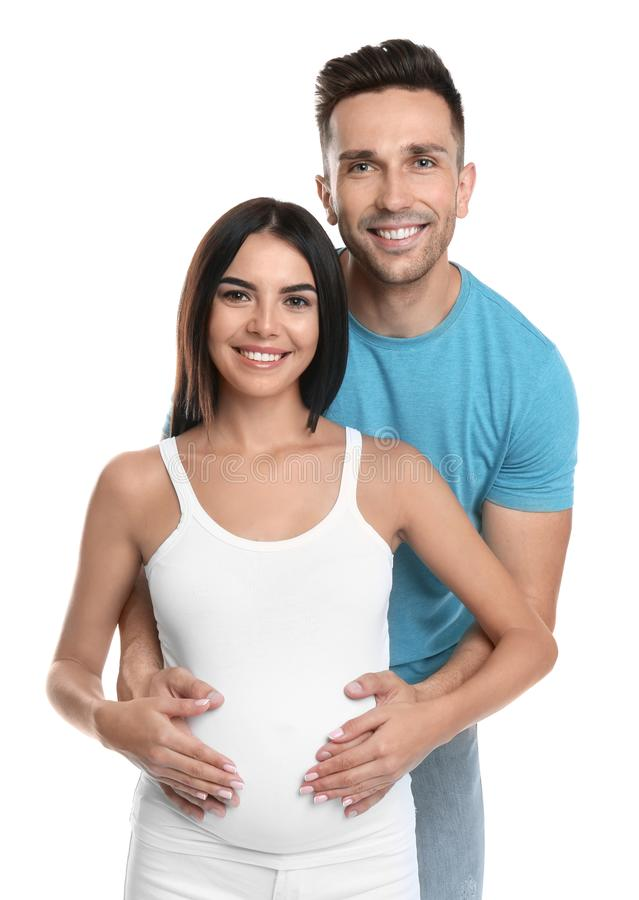 Young happy family holding pregnant belly on white stock image