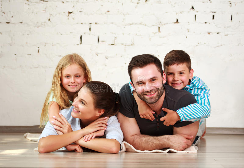 Young happy family parents and two children home studio stock photography