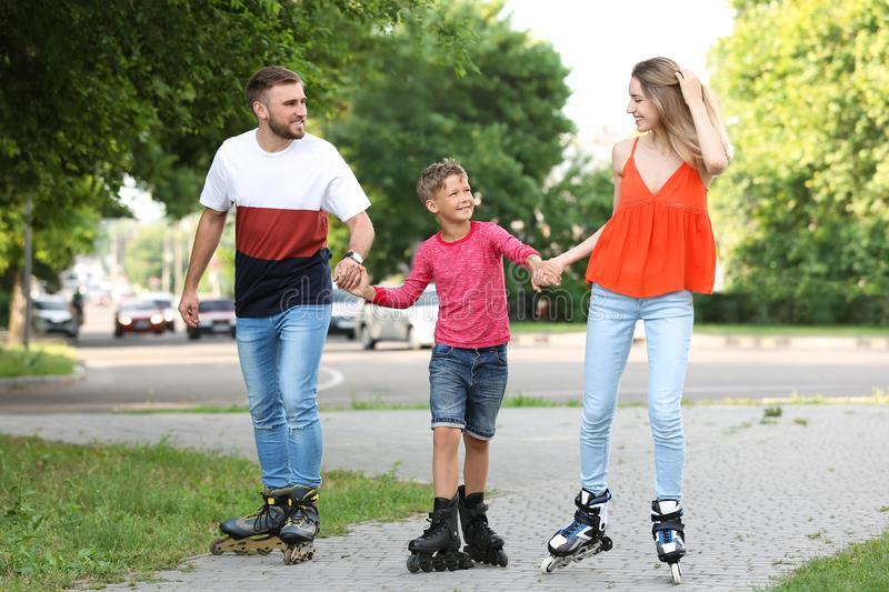 Young happy family roller skating on street royalty free stock photos