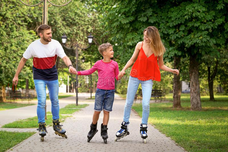 Young happy family roller skating in park stock photography
