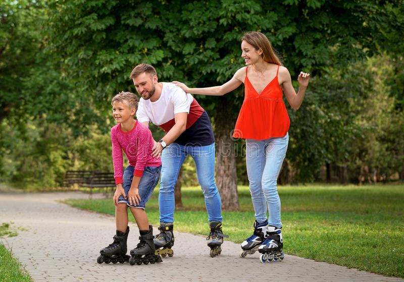Young happy family roller skating in park royalty free stock photos