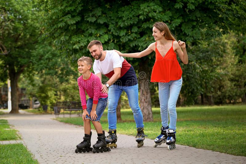 Young happy family roller skating in park royalty free stock photography