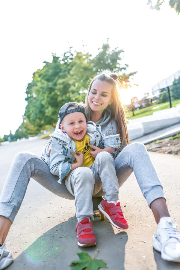 Young happy family smiling having fun, mother little boy 3-5 years old child, have rest on summer autumn day in city royalty free stock photos