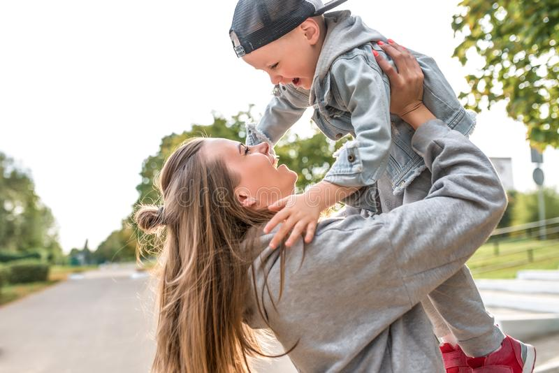 Young happy family smiling rejoicing having fun, mom throws up little boy 3-5 years old child, relax, summer autumn day stock photos