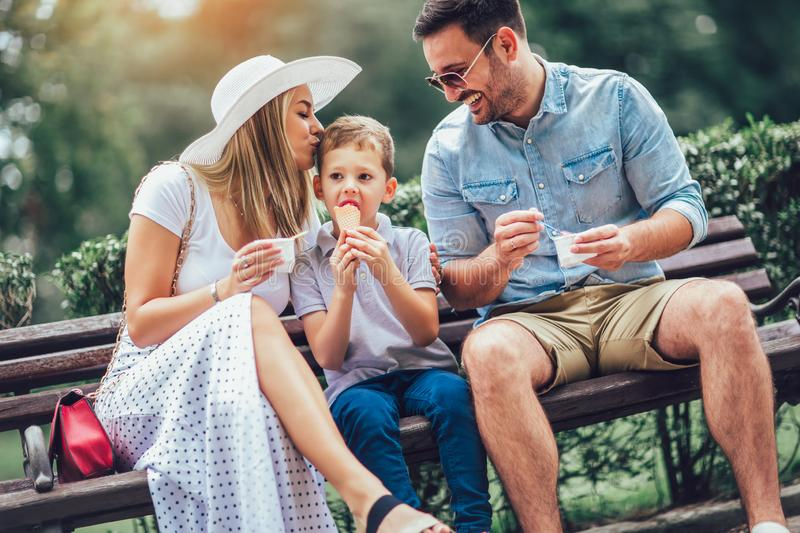 Happy family spending their weekend in the park. They are eating the ice cream stock images