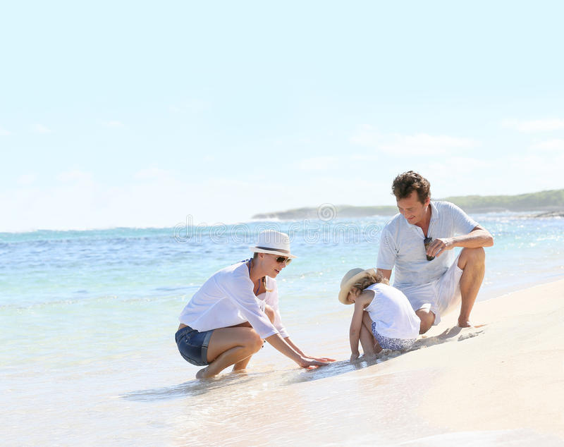Young happy family spending time on the beach royalty free stock image