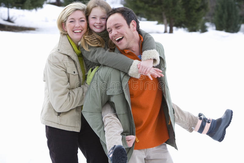 Young happy family standing in snow stock photography