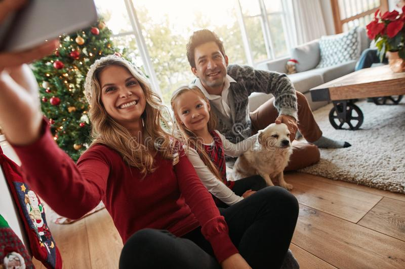 Young happy family taking selfie on Christmas eve stock photo