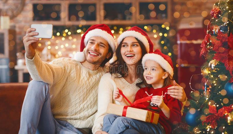 Young happy family of three taking selfie on Christmas eve royalty free stock image