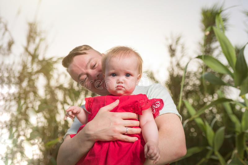 Young happy family walking outdoor. Father hold child on hands and rejoice royalty free stock images