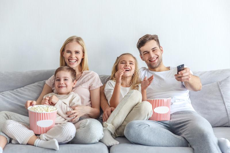 Young happy family watching movie on couch. At home royalty free stock photography