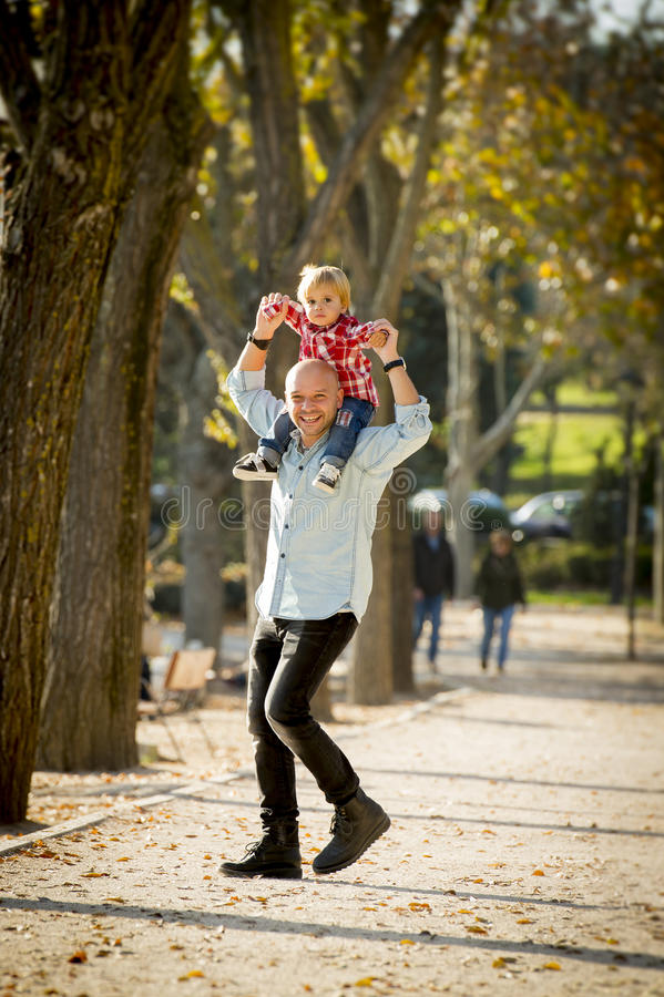 Young happy father carrying little son on shoulders having fun. Young attractive father carrying his happy little son on his shoulder walking together having fun royalty free stock photos