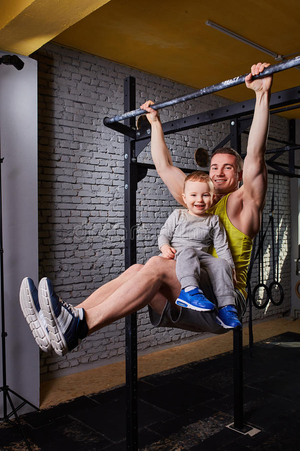 Young happy father doing pull ups on the bar with son on his legs at the cross fit gym against brick wall. Portrait of smiling father and his little son stock image