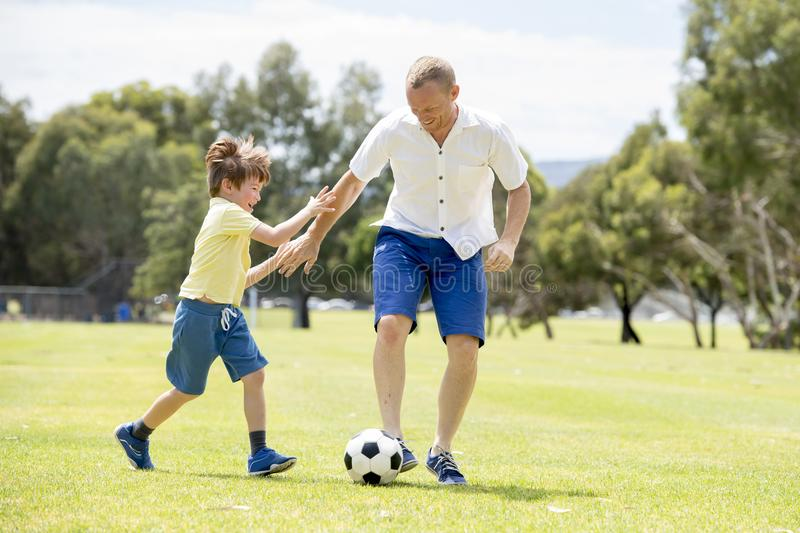 Young happy father and excited little 7 or 8 years old son playing together soccer football on city park garden running on grass k stock photos
