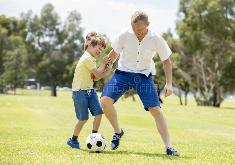 Young happy father and excited little 7 or 8 years old son playing together soccer football on city park garden running on grass k royalty free stock photo