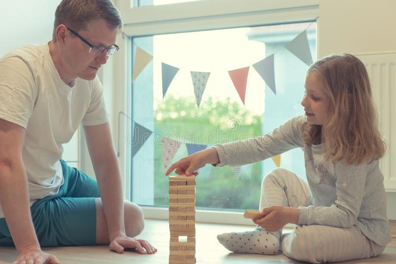 Young happy father playing with his cute daughter with wooden blocks stock image
