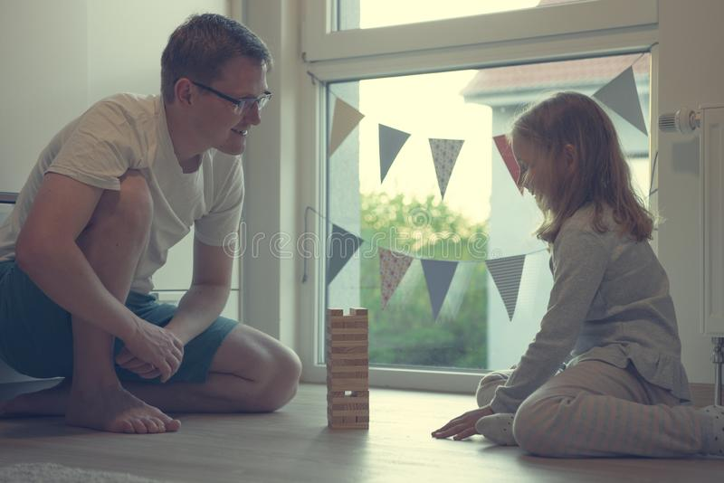 Young happy father playing with his cute daughter with wooden blocks royalty free stock photo