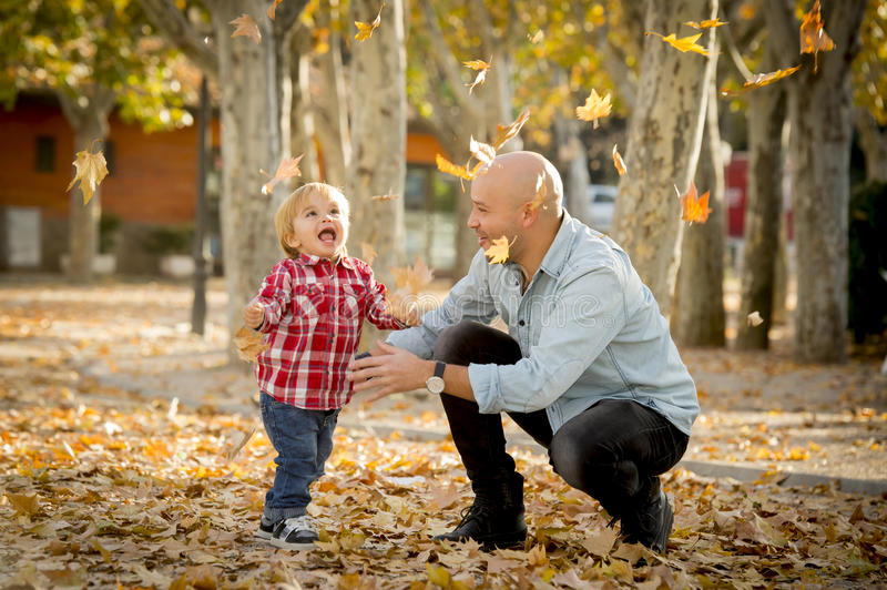 Young happy father playing with little cute son with tree leaves royalty free stock photography