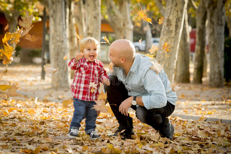 Young happy father playing with little cute son with tree leaves royalty free stock images