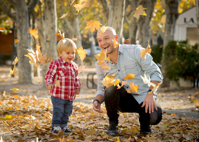 Young happy father playing with little cute son with tree leaves stock photos