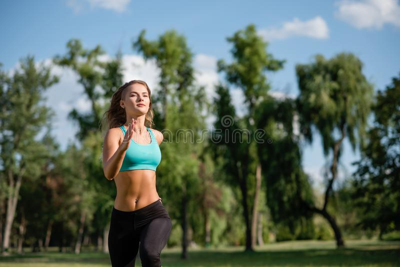 Young happy female runner running in city park. Healthy fitness woman jogging outdoors stock image
