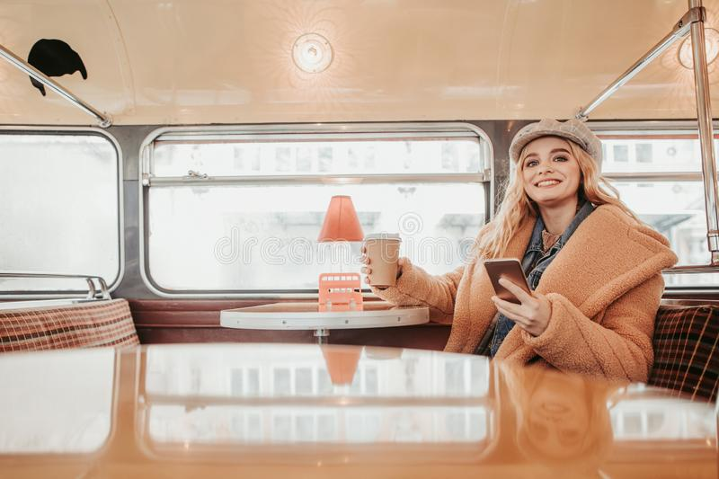 Young happy female sitting with phone in bus cafe royalty free stock photography