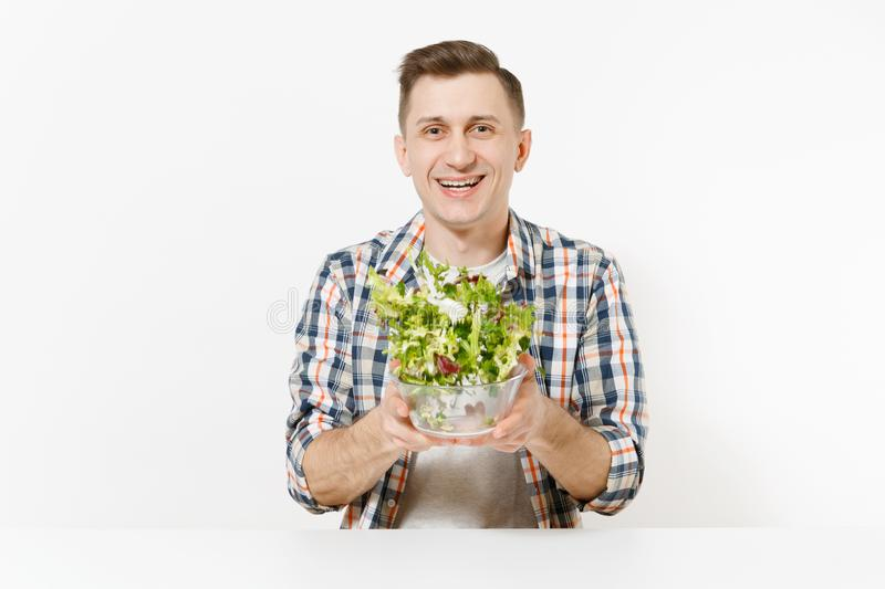 Young happy fun man sitting and throwing up salad from glass bowl isolated on white background. Proper nutrition. Vegetarian food, healthy lifestyle, dieting stock photos
