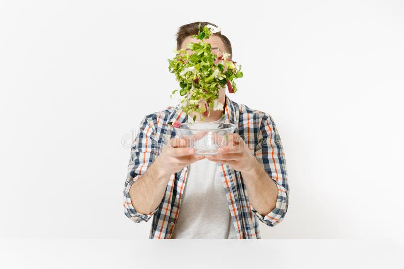 Young happy fun man sitting and throwing up salad from glass bowl isolated on white background. Proper nutrition. Vegetarian food, healthy lifestyle, dieting stock image
